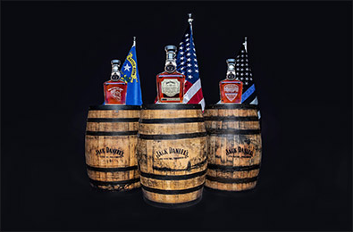 Three barrels with a bottle of Jack Daniel's on each